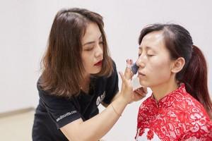 """幕后的化妆师为""""红歌传唱·激情飞扬合唱比赛""""选手化妆"""